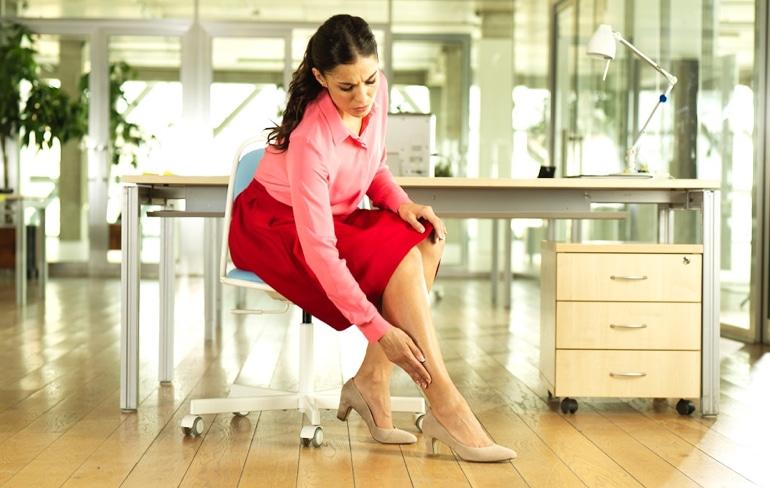 Žena sedí na židli v kanceláři a dotýká se nohy.