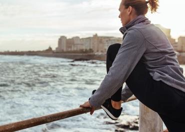 Žena si protahuje unavené nohy, poté co se byla proběhnout v rámci prevence žilní nedostatečnosti.