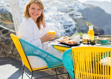 Rozzářená smějící se žena si užívá zdravou snídani jako prevenci žilní nedostatečnosti.