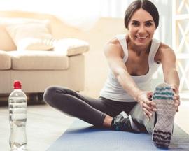 Ženy provádí žilní gymnastiku na jógové podložce jako prevenci těžkých nohou.