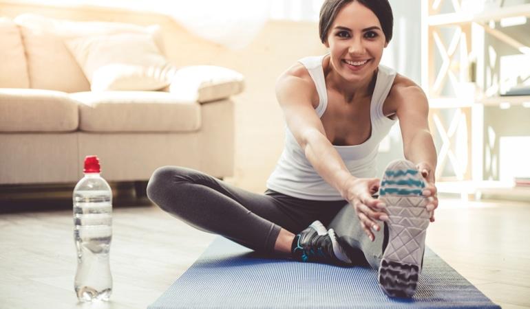 Žena si v předklonu protahuje obě nohy na cvičební podložce, aby předešla žilní nedostatečnosti.