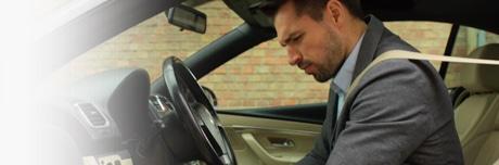 Muž s pocitem těžkých nohou sedící v autě
