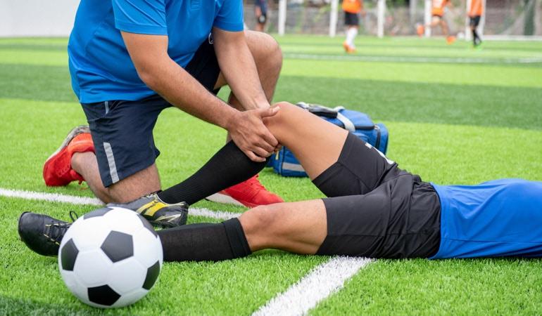 Zraněný fotbalista a lékař s přípravkem Lioton® 100 000 gel